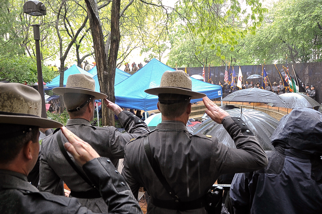 New York State Troopers salute as the colors are presented at the Police Officers' Memorial Remembrance Ceremony.